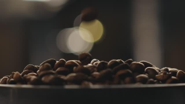 stockvideo's en b-roll-footage met close-up van gebrande koffiebonen die vallen - koffie drank