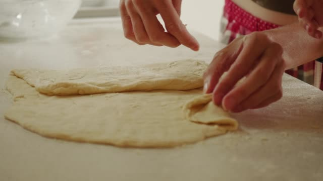 closeup of rolling out pastry by mother and child hands in kitchen - spanking stock-videos und b-roll-filmmaterial