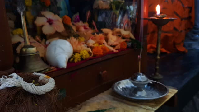 closeup of sacred thread (janeu/janev) with beetle nut kept on holy dried coconut (kalash) during worship/prayer with defocused view of flowers, brass bell, conch shell, burning diya/ oil lamp at the background - conch stock videos & royalty-free footage