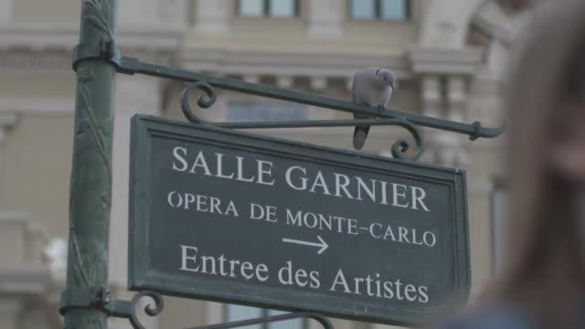 vidéos et rushes de close-up of salle garnier, opera de monte-carlo, entrée des artistes sign and a pigeon perched on sign - opéra style musical