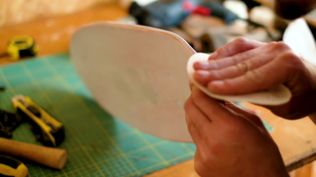 close-up of sanding skateboard by hand - part of stock videos & royalty-free footage