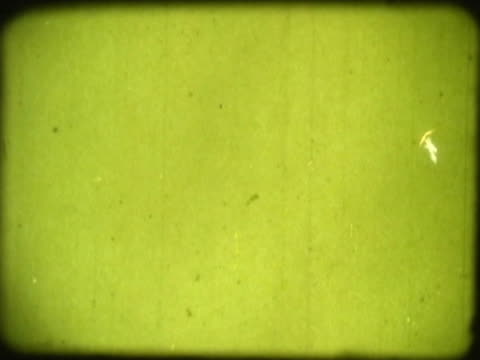 Close-up of scribbles and dust on a green film leader