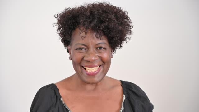 stockvideo's en b-roll-footage met close-up van hogere zwarte vrouw in geschepte halsblouse - lage ronde hals
