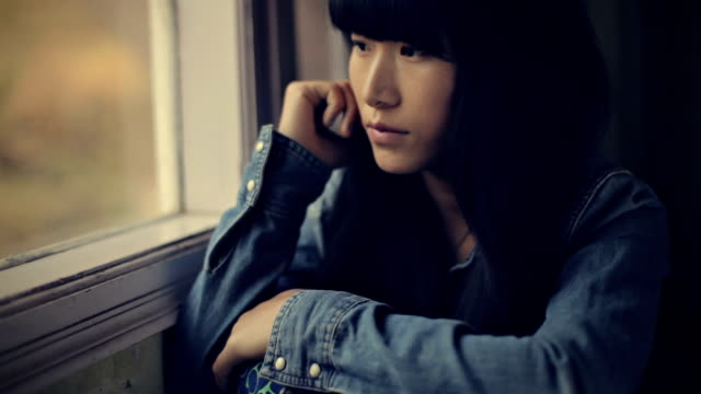 close-up of serene asian girl sitting near window. - looking away stock videos & royalty-free footage