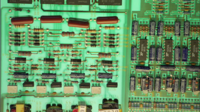 Close-up of sharp components of a circuit board slowly blur.