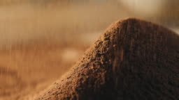 Close-up of sifting cocoa powder sieve on a brown background