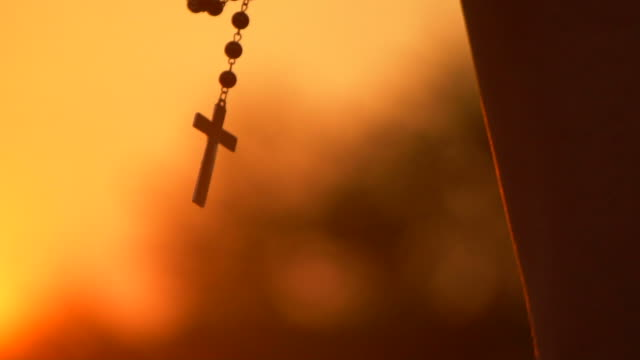 closeup of silhouette cross hanging at sunset - cristianesimo video stock e b–roll