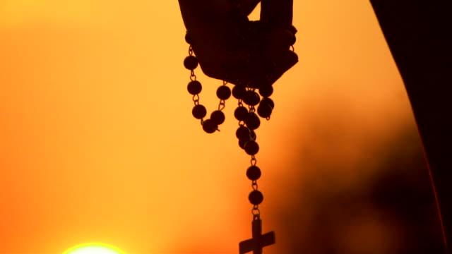 日没時にぶら下がっているシルエットクロスのクローズアップ - イエス キリスト点の映像素材/bロール