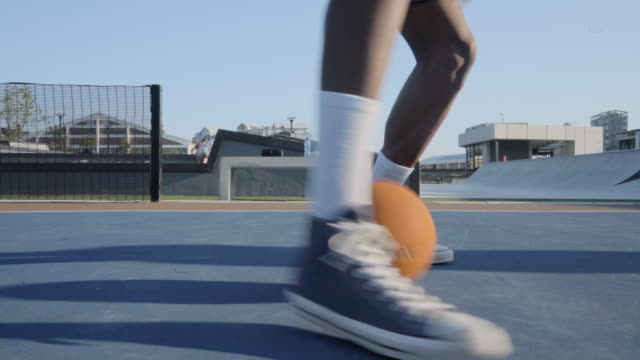 closeup of skilled basketball player dribbling through opponents legs - basketball player stock videos & royalty-free footage