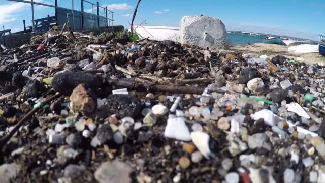 vídeos de stock, filmes e b-roll de close-up of small plastic pellets, known as 'nurdles', washed up on a beach near portsmouth - poluição do plástico