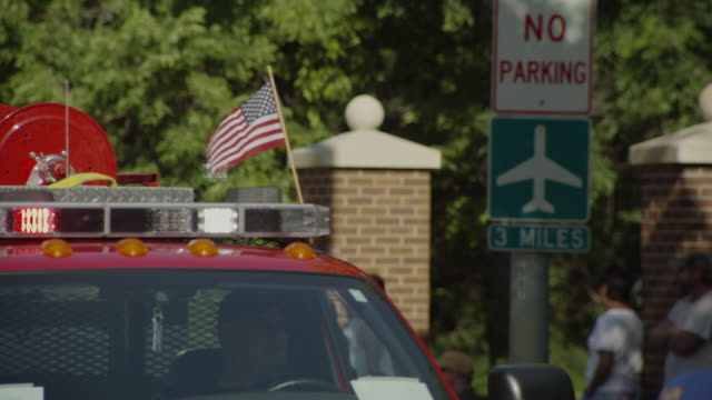 closeup of small united states of america flag waves and is attached to a firetruck driving down the street in a small town parade. - 消防車点の映像素材/bロール