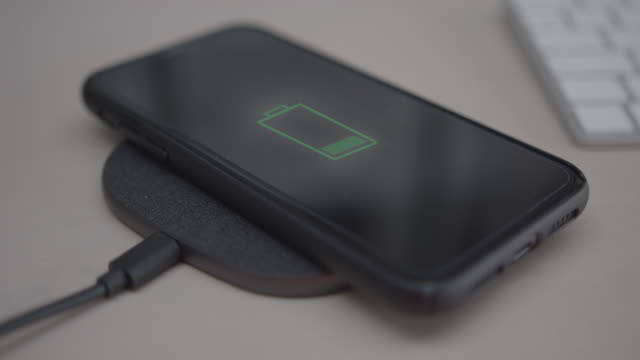 vídeos de stock e filmes b-roll de close-up of smart phone connected to portable charger - fornecimento de energia