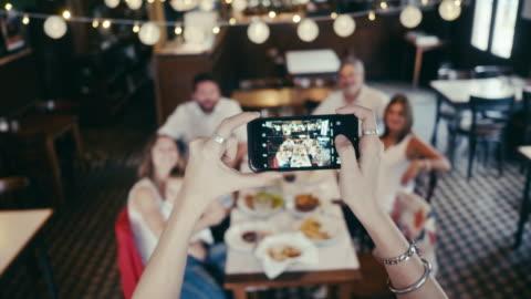 vídeos y material grabado en eventos de stock de primer plano del teléfono inteligente tomando una foto de grupo en el restaurante - plato de comida