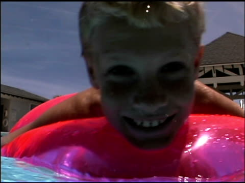 close-up of smiling boy floating in pink innertube in swimming pool. - see other clips from this shoot 1135 stock videos & royalty-free footage