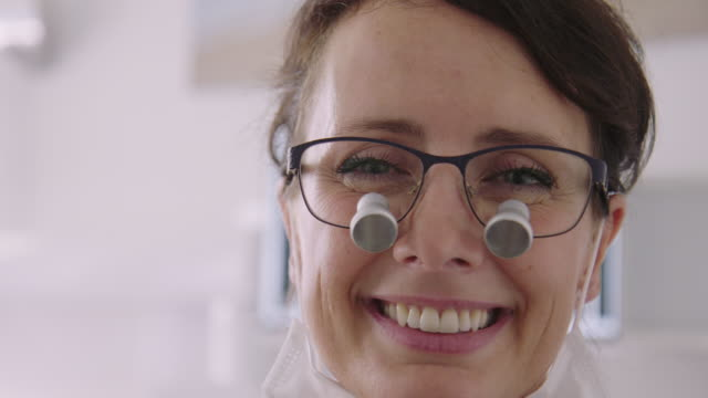 vídeos de stock e filmes b-roll de close-up of smiling dentist against medical x-ray - dentista