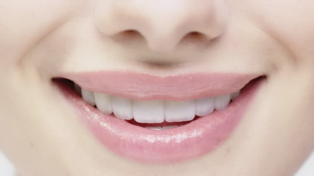 close-up of smiling woman biting her glossy lips - sorridere video stock e b–roll