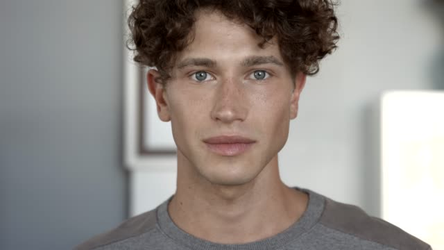 stockvideo's en b-roll-footage met close-up of smiling young man with curly hair - milleniumgeneratie