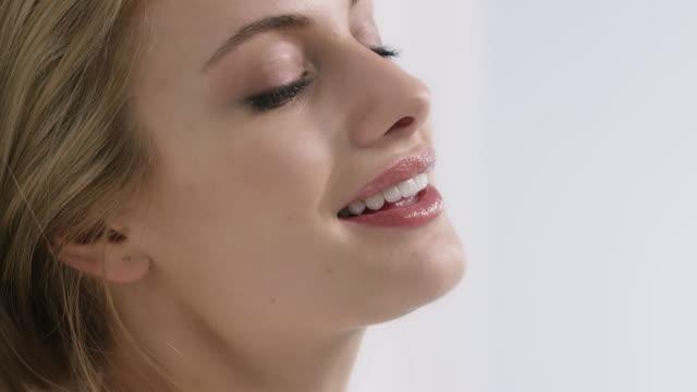 nahaufnahme der lächelnde junge frau, die an die wand gelehnt - kosmetik stock-videos und b-roll-filmmaterial