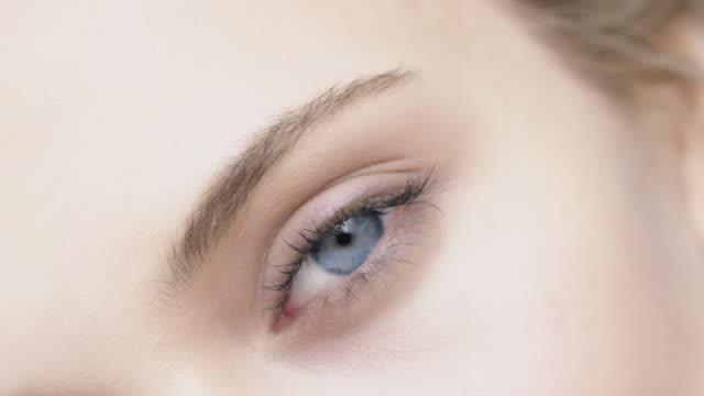 stockvideo's en b-roll-footage met close-up van lachende jonge vrouw met blauwe ogen - menselijke neus