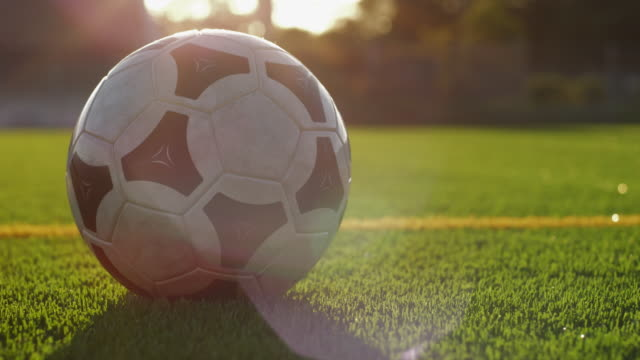 Close-up of soccer ball on stadium field; soccer players kicks ball out of frame