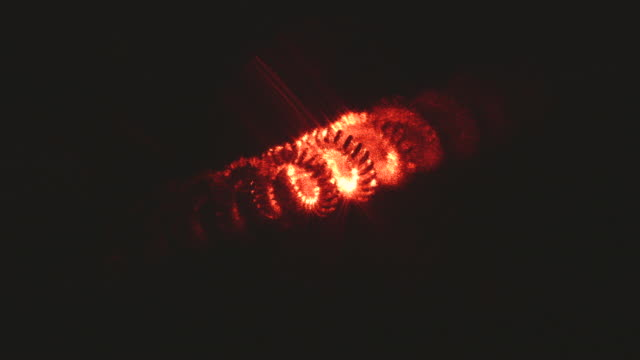 close-up of straight red laser light and diffracted red laser light travelling through a fuzzy coil. - schurke stock-videos und b-roll-filmmaterial