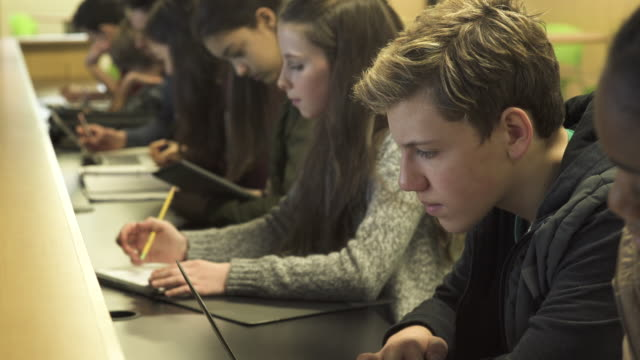 Close-up of students learning in class room