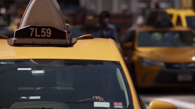 vídeos y material grabado en eventos de stock de closeup of taxi driver waiting at street light as traffic continues behind him. - taxista
