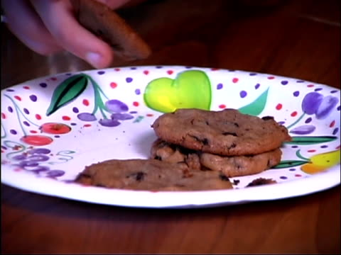 close-up of teen boy's hand taking a cookie from a plate. - unknown gender stock videos & royalty-free footage