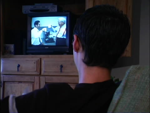 close-up of teen boy's head as he sits on couch and watches television. - männlicher teenager allein stock-videos und b-roll-filmmaterial