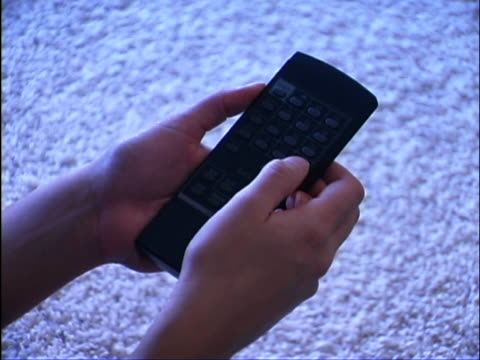 close-up of teen girl's hands holding a t.v. remote controller.,she keeps pressing buttons on the remote control. - unknown gender stock videos & royalty-free footage