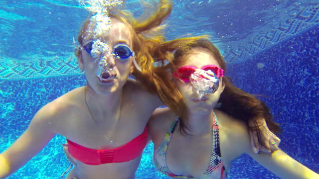 close-up of teenage girls blowing bubbles underwater - tonårsflickor bildbanksvideor och videomaterial från bakom kulisserna
