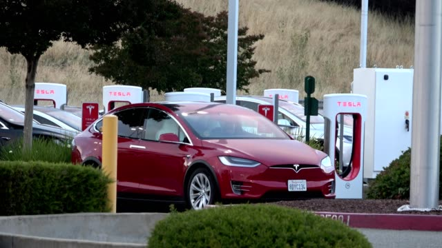 vídeos de stock, filmes e b-roll de closeup of tesla model 3 electric car from tesla motors plugged in and charging at a supercharger electric vehicle charging station in pleasanton... - carregamento eletricidade