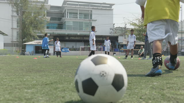 close-up of the ball with a child playing soccer in the background. - education building stock videos & royalty-free footage