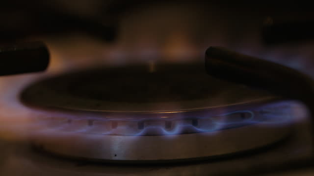 vídeos de stock, filmes e b-roll de close-up of the blue flames created by a gas stove being lit and turned off again, uk. - energy efficient