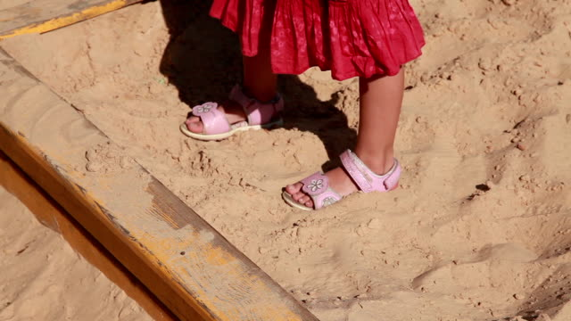 close-up of the child's feet in the sandbox - sand pit stock videos and b-roll footage
