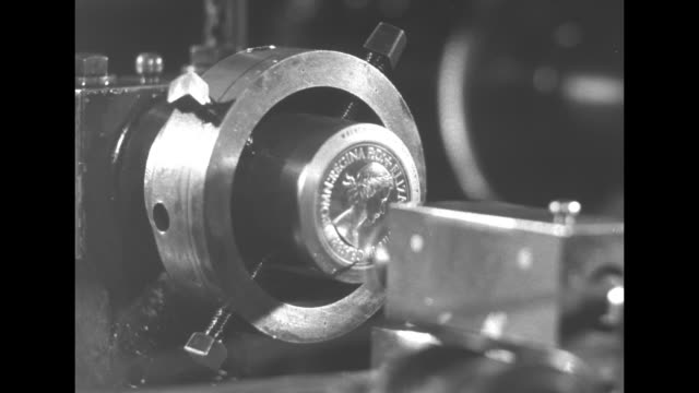 vs closeup of the elizabeth 'portrait' on the coin die turning slowly in a circular holder as the image is carved an inspector closely examines the... - geldpresse stock-videos und b-roll-filmmaterial