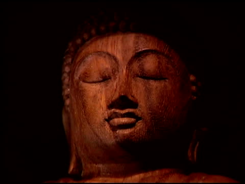 close-up of the face of a buddhist statue made out of wood. - weibliche figur stock-videos und b-roll-filmmaterial