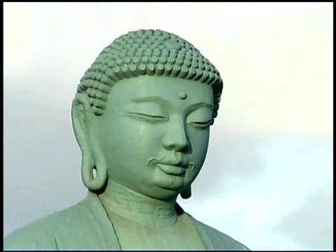 close-up of the face on a buddha statue against a cloudy sky. - weibliche figur stock-videos und b-roll-filmmaterial