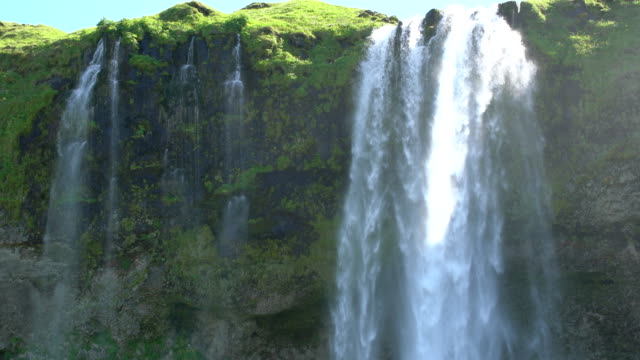Close-up of the falling waters of Seljalandsfoss waterfall in Iceland during a sunny bright day