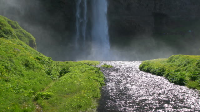 Close-up of the falling waters of the Seljalandsfoss waterfall in Iceland during a sunny bright day