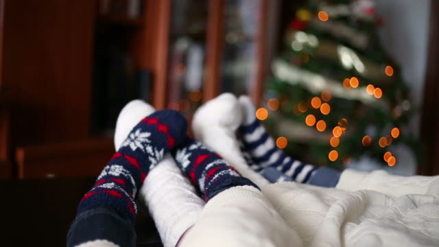 close-up of the feet of a family in christmas socks lying in the living room sharing time together covered by a blanket next to the christmas tree - sock stock videos & royalty-free footage
