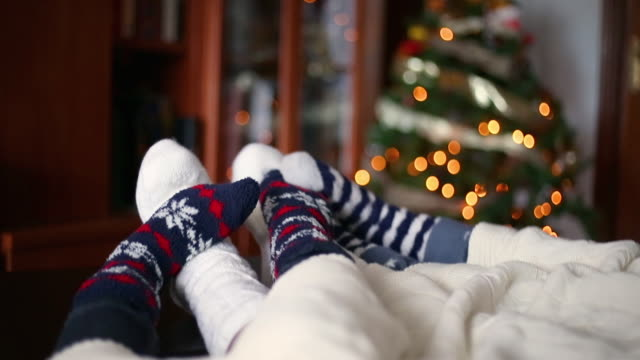 close-up of the feet of a family in christmas socks moving under a blanket next to the christmas tree - real people stock videos & royalty-free footage