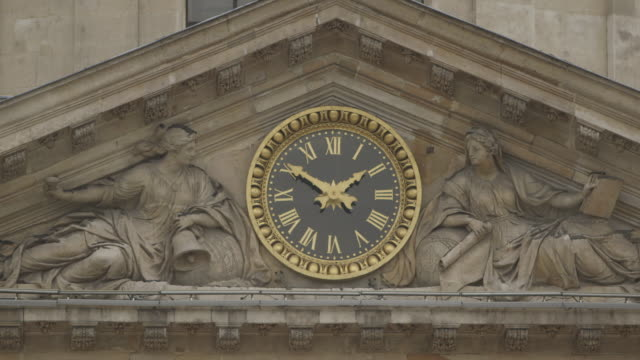 Close-up of the gold-coloured clock face of the Institut de France surrounded by classical stonework reading ten to two, Paris, France.