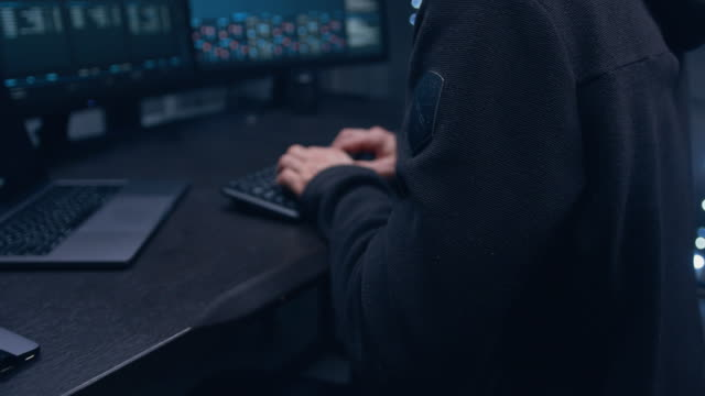 vidéos et rushes de gros plan des mains du pirate tapant sur le clavier, la caméra s'éloigne du plan général et le plan général devient flou. - casser les codes