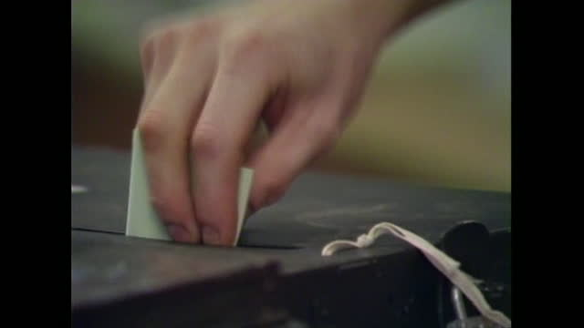 close-up of the hand of a young woman pushing a slip of paper through the slot of a ballot box as a union votes on industrial action, uk; 1988. - local politics stock videos & royalty-free footage