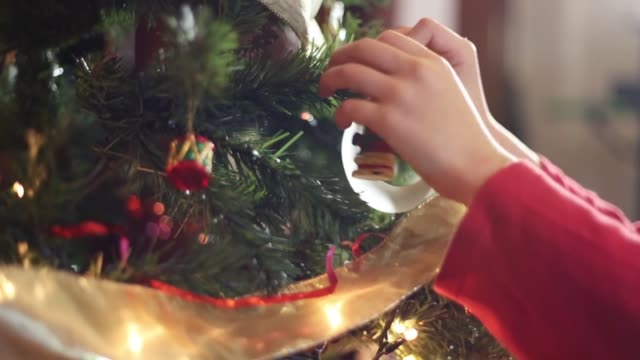 closeup of the hands of a girl hanging christmas ornaments on the christmas tree - christmas tree stock videos & royalty-free footage