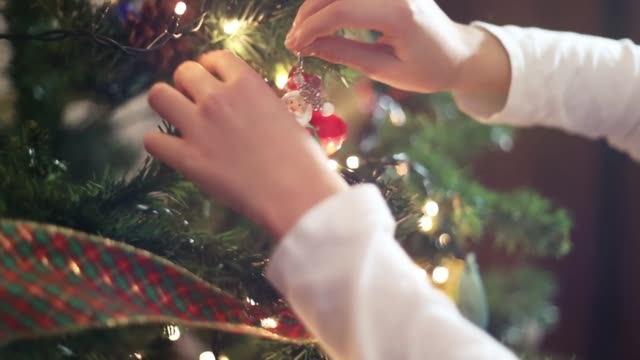 vídeos de stock, filmes e b-roll de closeup of the hands of a little girl putting christmas ornament on the christmas tree at home. - ornament