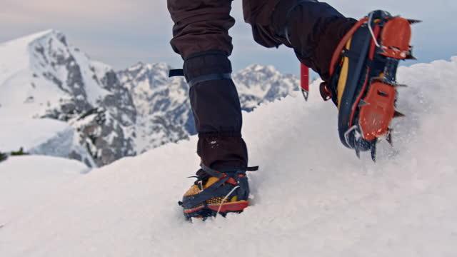 vídeos y material grabado en eventos de stock de primer plano de las piernas de un excursionista caminando sobre la montaña cubierta de nieve - nevosa