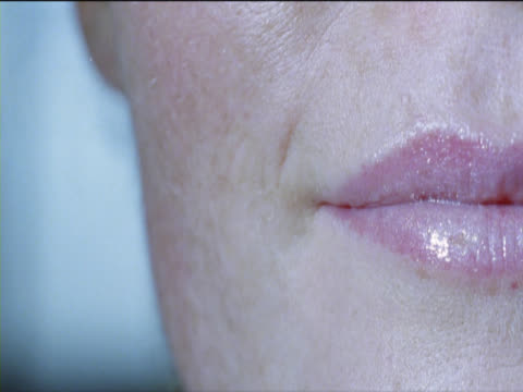 vidéos et rushes de close-up of the mouth of a young woman smiling - bouche humaine