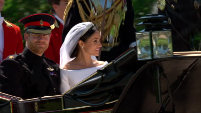 Closeup of the newlywed Duke and Duchess of Sussex travelling by horse and carriage along the Long Walk in Windsor Great Park